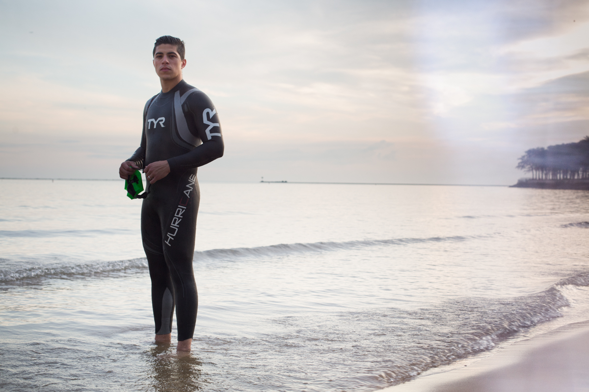 man-poses-for-photo-in-his-wetsuit